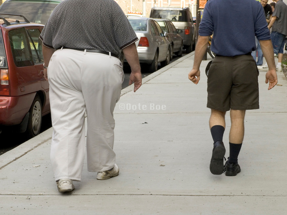 obese man walking next to a normal person.