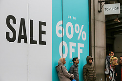 "© Licensed to London News Pictures. 23/12/2018. London, UK. Shoppers outside TopShop with a large window display showing ""Sale 60% Off"". Last minute Christmas shoppers take advantage of pre-Christmas bargains in London's Oxford Street. Fewer shoppers have been reported shopping in Britain's high streets as online sales increase. Photo credit: Dinendra Haria/LNP"