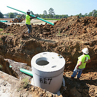 Crews with Eubanks Constructin continue to put down sewer lines along Ida Street in Tupelo as the now vacnat lots will soon be redeveloped.