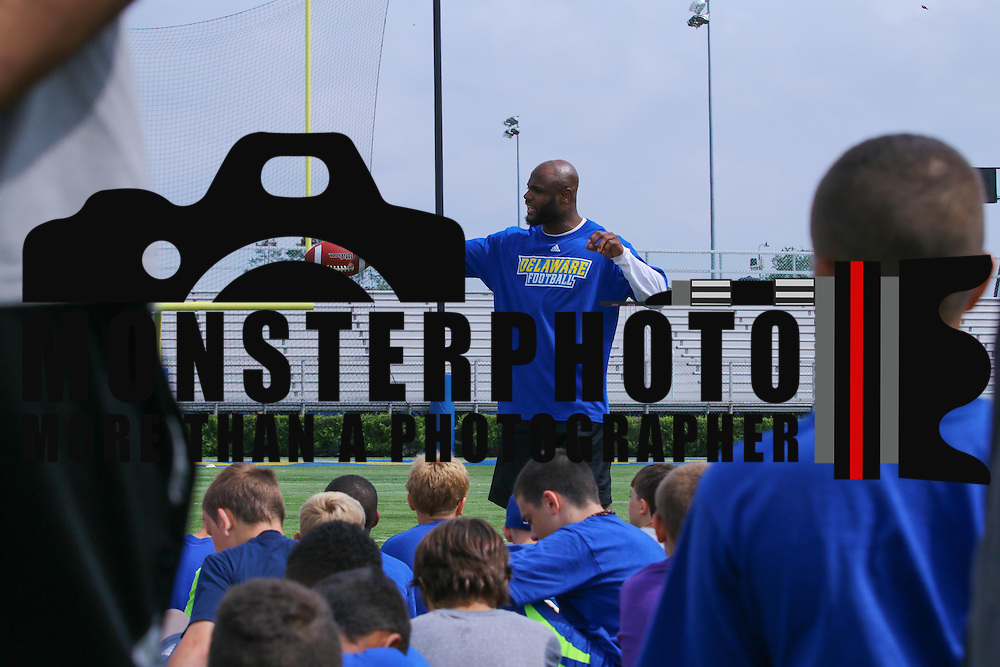 Former UD football player and current Indianapolis Colts defensive back Mike Adams, CENTER, gives remarks during UD youth football camp Friday, June 26, 2015, at Delaware Stadium on The Campus of The University of Delaware in Newark, Delaware.