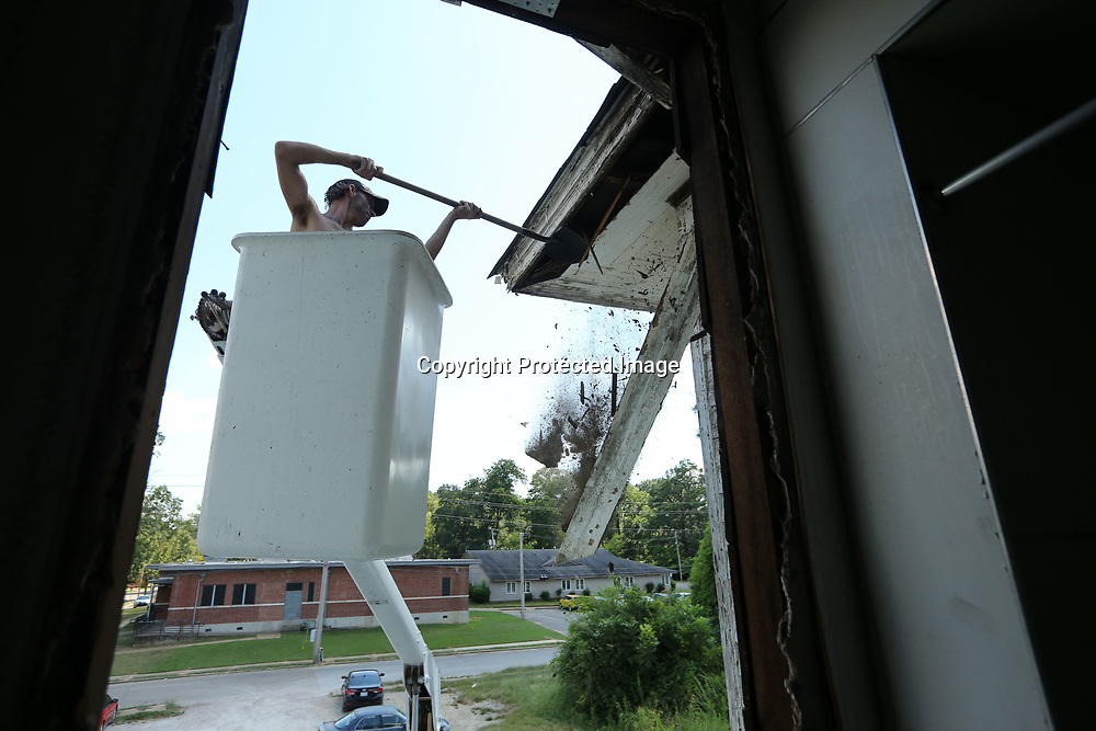 Carl Moncrief, an employee for Wooten Construction, knocks away the old rotten siding from the Spain House in Tupelo on Thursday as the crew works to prep the home for new siding to be added.