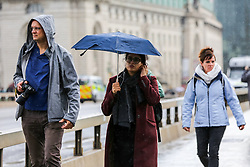 © Licensed to London News Pictures. 16/10/2019. London, UK. A woman shelters from rain underneath an umbrella on Westminster Bridge. According to the Met Office more rain is forecasted for the next few days. Photo credit: Dinendra Haria/LNP