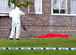 © under license to London News Pictures. 14/04/2011. A police forensic officer examines the gun and victim of a fatal shooting in the Clapham Park area of London.   A paramedic was reportedly shot at but uninjured. The incident is very close to Stockwell where a 5 year old was shot in the chest recently. Photo credit should read Cliff Hide/LNP