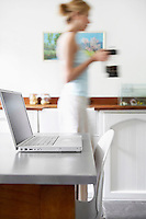 Woman in kitchen with coffee percolator walking by laptop focus on laptop