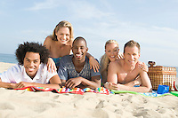 Group of young people lying on sand
