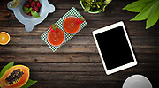Fresh fruit  and smoothies on wood background with customizable device, top view and copy space.