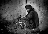 Kabuli man displays a hit of heroin on the foil from a cigarette pack as he prepares to smoke it in filthy, abandoned chamber in old city of Kabul, Afghanistan.