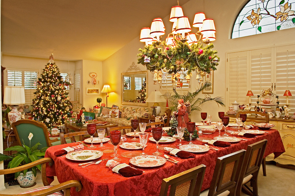 Dining room table set for Christmas dinner with tree, decorations and gifts in living room of house in southern California, USA.