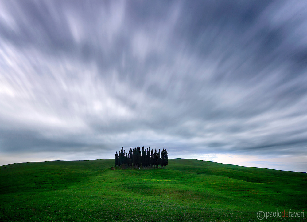 The most photographed bunch of cypress tress in the world is atop a hill not far from San Quirico d'Orcia, a nice medieval town in Orcia Valley, Tuscany. Taken at dawn at the end of April. I had noticed the clouds were travelling fast in the sky, so I decided to record this motion with a very long exposure, using a 10 stops ND filter.