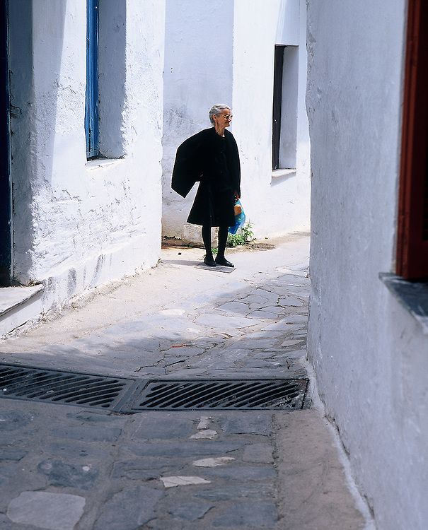Old woman standing in alleyway on the island of Mykonos, Greece