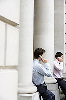Two businessmen on cell phones sitting on pillars outside building
