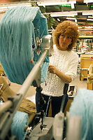 Woman operating a machine winding wool into skeins . Robin Wools Ltd also known as Robert Glew Wool Industries Ltd
