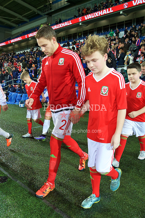 CARDIFF, WALES - Friday, November 13, 2015: Wales' Chris Gunter walks out with a mascot before the International Friendly match against the Netherlands at the Cardiff City Stadium. (Pic by David Rawcliffe/Propaganda)