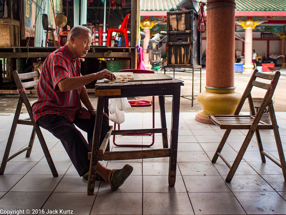 30 JUNE 2016 - BANGKOK, THAILAND: A man plays Chinese checkers by himself at a Chinese shrine in Bangkok.        PHOTO BY JACK KURTZ
