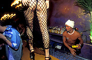 A barman makes drinks as a woman in g-string and fishnet stockings walks along the top of the bar, 2000's