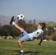 """A young boy performs a soccer """"bicycle kick"""" in a park"""