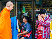25 AUGUST 2016 - BANGKOK, THAILAND: A monk on his morning alms rounds solicits a donation from a vendor in the flower market in Bangkok. Most Thai males enter the monastery and become monks or novices (young monks) at some point in their lives.         PHOTO BY JACK KURTZ