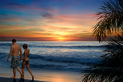 Couple walking along a tropical beach at sunset