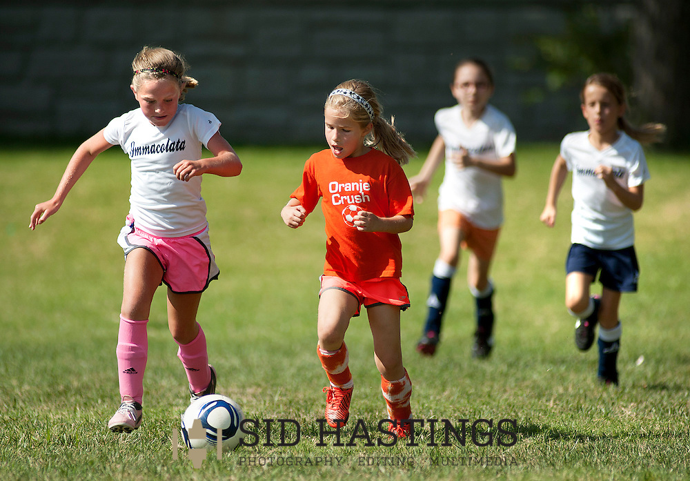 28 JULY 2013 -- RICHMOND HEIGHTS, Mo. -- Immacolata third grade soccer player Clare Barry (left) and Oranje Crush player Janie Schnell push the ball upfield during the Summer Watermelon League, sponsored by New Dimensions Soccer, at St. Luke the Evangelist Catholic Church in Richmond Heights, Mo. Sunday, July 28, 2013. Teams play four versus four, without a goalie, and don't keep score. Photo © copyright 2013 Sid Hastings.