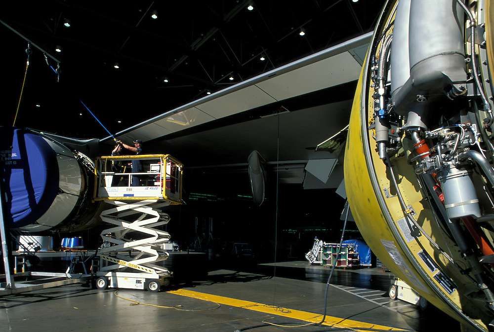 USA, Washington, Everett, Boeing workers work on GE jet engine on Boeing 747 cargo jet in final stage of assembly line