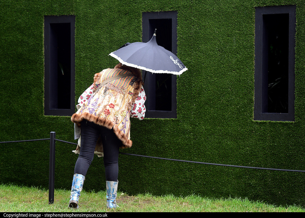 © Licensed to London News Pictures. 02/07/2012. East Molesey, UK A woman looks into a pavilion in a garden. The RHS Hampton Court Palace Flower Show 2012. The show runs 3-8 July, 2012. Photo credit : Stephen Simpson/LNP