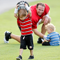 July 28, 2012; Metairie, LA, USA; Baylen Brees son of New Orleans Saints quarterback Drew Brees takes off with his helmet as Brees watches and plays with his youngest son Bowen following a training camp practice at the team's practice facility. Mandatory Credit: Derick E. Hingle-US PRESSWIRE