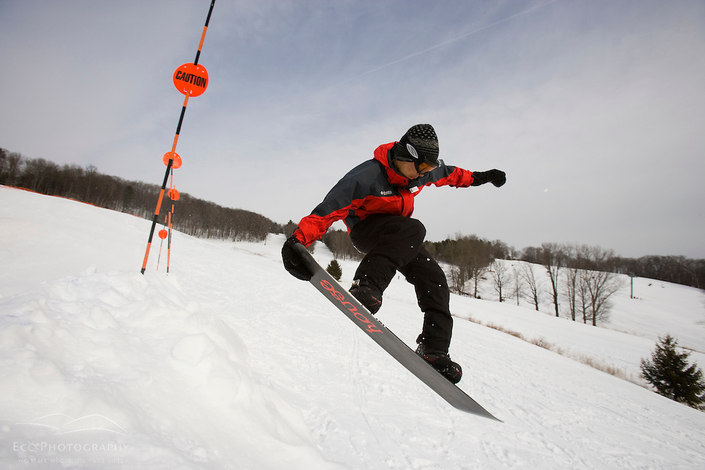 Getting some air on a snowboard at the Quechee Ski Hill in Quechee, Vermont.