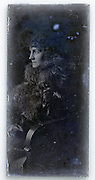 vintage portrait of young adult woman in fur coat sitting in chair