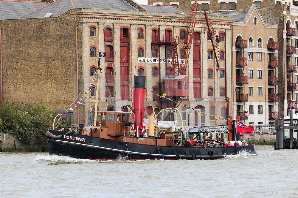 © Licensed to London News Pictures. 04/08/2017. LONDON, UK.  Steam Tug (ST) Portwey steams along the River Thames past historic riverside wharfs in London, travelling to Gravesend to take part in a series of events marking her 90th birthday, including a salute by Commander Richard Pethybridge at the Royal Navy's HMS President on the way. The ST Portwey was built on the Clyde in 1927, came under the command of the Royal Navy during the Second World War when she was based in Dartmouth and carried out rescues of vessels and crews sunk by enemy action in the Channel and is the only twin screw, coal fired steam tug still active in the whole of the United Kingdom.  Photo credit: Vickie Flores/LNP