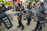 24 MAY 2014 - BANGKOK, THAILAND: Thai riot police walk down Phahon Yothin Street in Bangkok past an anti-coup protestors. There were several marches in different parts of Bangkok to protest the coup that unseated the popularly elected government. Soldiers and police confronted protestors and made several arrests but most of the protests were peaceful. The military junta also announced that firing of several police commanders and dissolution of the Thai Senate. The junta also changed its name from National Peace and Order Maintaining Council (NPOMC) to the National Council for Peace and Order (NCPO).   PHOTO BY JACK KURTZ