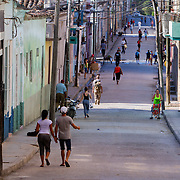 Light traffic allows people to use streets as sidewalks. Cubans manage their daily life in the colonial city of Matanzas walking or riding bicycles to most places and doubling up on old classic cars and motorcycles. Photography by Jose More