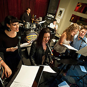 """December 5, 2013 - New York, NY: Members of the NBC musical drama television series """"Smash"""" including, from left, Julia Mattison, Molly Hager, Shannon Ford (drums), Carrie Manolakos, Dennis Michael Keefe (bass), Monet Julia Sabel, Eric Michael Krop, and Hiroko Taguchi (violin), rehearse at Smash Studios at 36th Street in Manhattan on Thursday afternoon in preparation for their cabaret performance of """"HIT LIST,"""" which will premiere Sun, Dec 8 at 54 Below. CREDIT: Karsten Moran for The New York Times"""