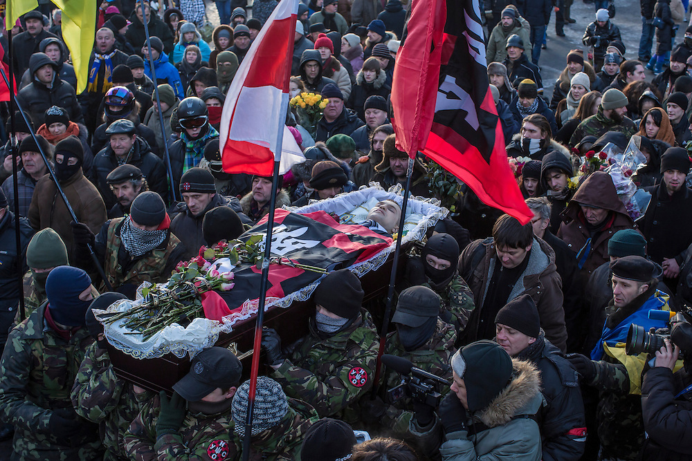 KIEV, UKRAINE - JANUARY 26: Men carry a casket containing the body of Mikhail Zhiznevsky, 25, an anti-government protester who was killed in clashes with police, through the streets of downtown Kiev after a memorial service in his honor on January 26, 2014 in Kiev, Ukraine. After two months of primarily peaceful anti-government protests in the city center, new laws meant to end the protest movement have sparked violent clashes in recent days. (Photo by Brendan Hoffman/Getty Images) *** Local Caption *** Mikhail Zhiznevsky