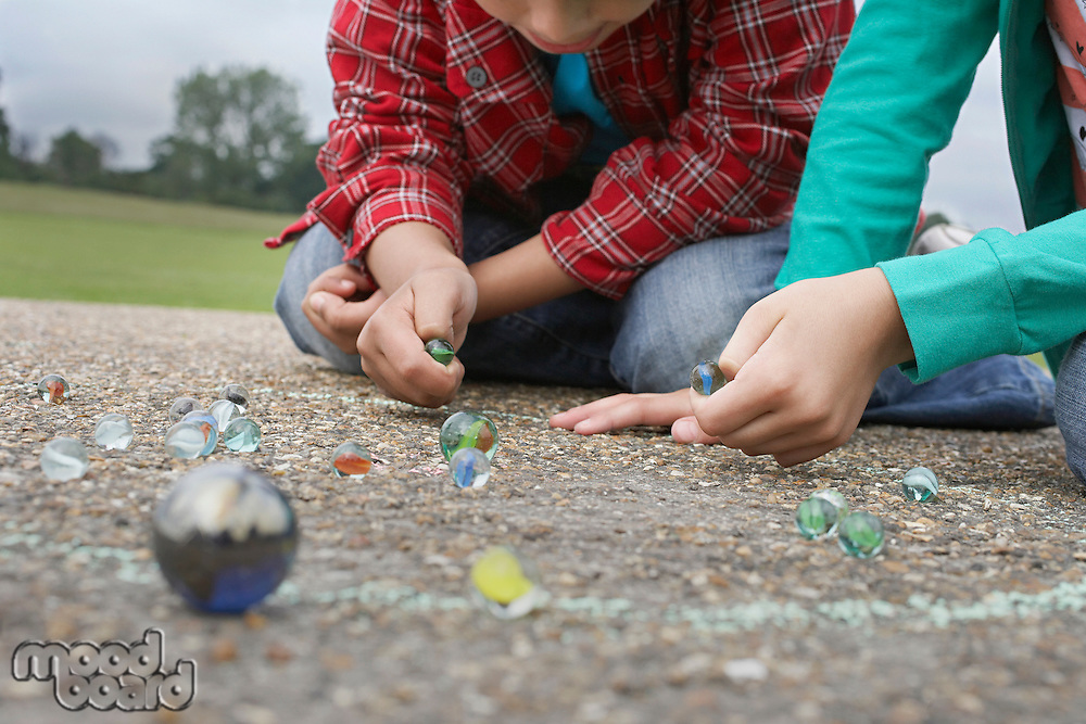 Children (7-9) playing marbles lying in playground