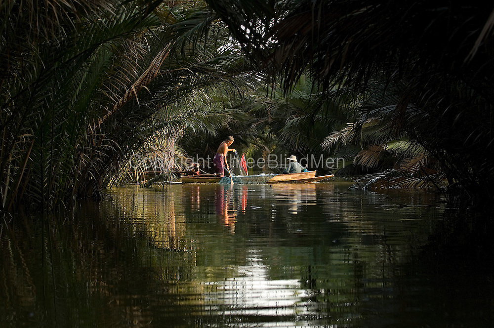Mr. Plang and Mrs. Lah net fish on Klong Na Klue, district of Phra Samuthjedi, Samuthprakarn Province.