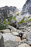 A woman hiking across a boulder field near Colchuk Lake below Aasgard Pass in the Cascades mountains of Washington State, USA.