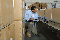Man inspecting boxes on conveyor belt in distribution warehouse