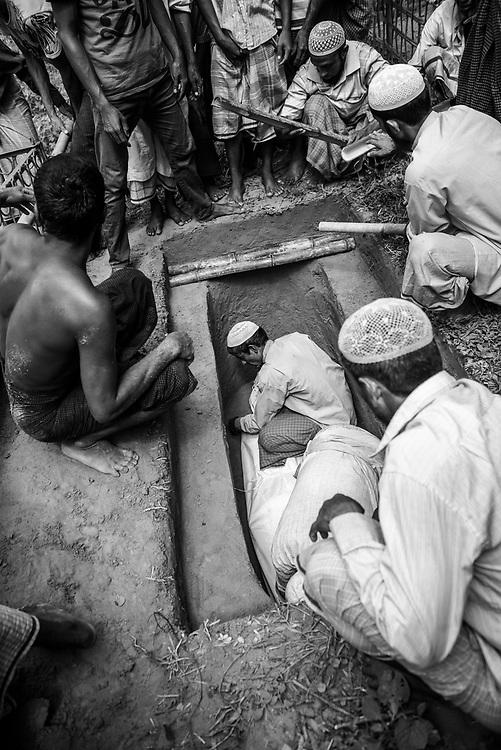 Rohingya refugees lay a body in a grave at Kutupalong refugee camp, Bangladesh (October 29, 2017)