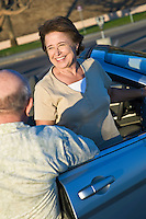 Senior couple standing outside convertible, elevated view