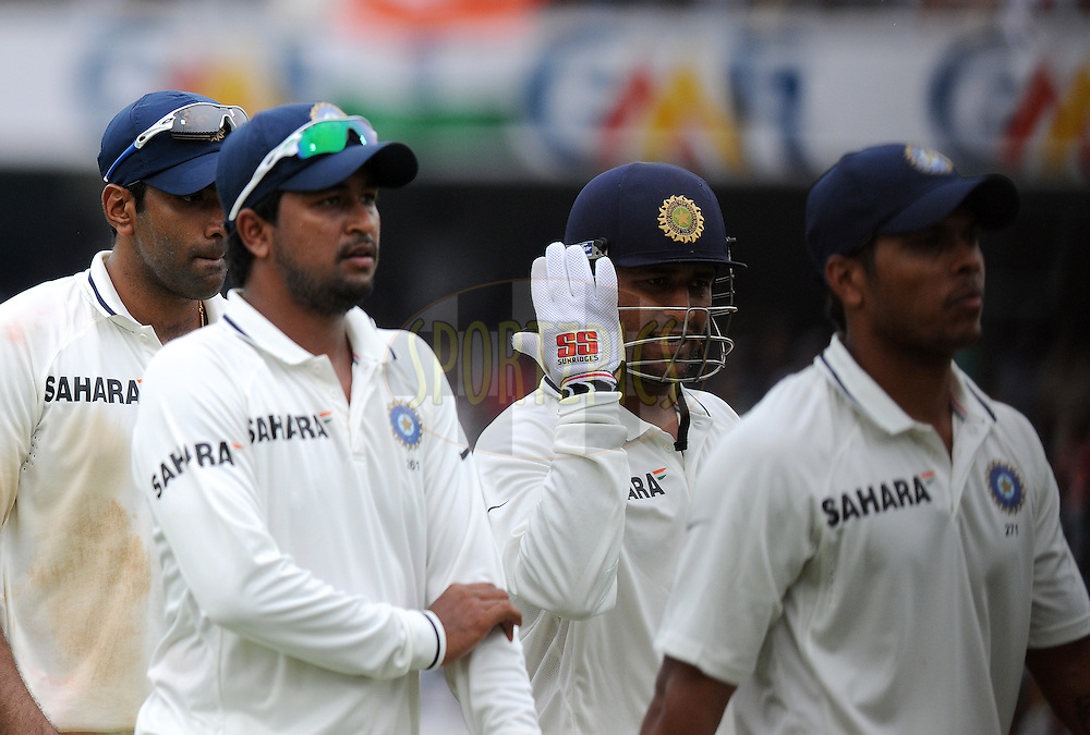 Pragyan Ojha of India, and Ravichandran Ashwin of India  walk to the pavilion with captain Mahendra Singh Dhoni during the tea break on day four of the first test match between India and New Zealand held at The Rajiv Gandhi International Stadium in Hyderabad, India on the 26th August 2012..Photo by: Pal Pillai/BCCI/SPORTZPICS