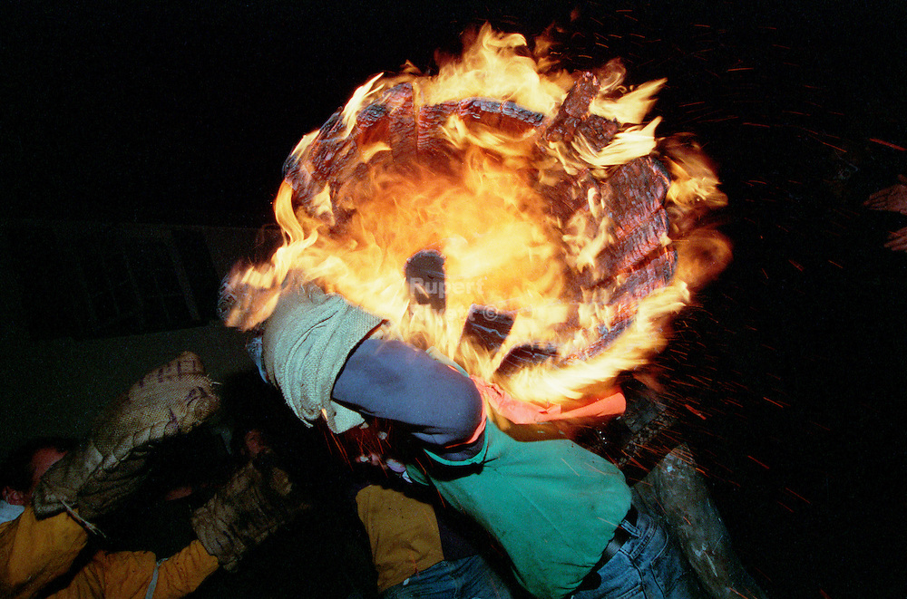 A flaming barrel ! Only hessian sacks protect the barrel mans hands from burning.