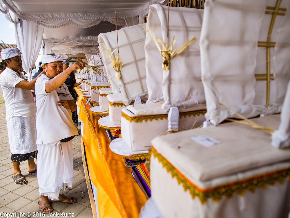 14 JULY 2016 - UBUD, BALI, INDONESIA: A Hindu priest blesses a coffin containing human ashes before cremation. The coffin, and nearly 100 others, will be burned in a mass cremation ceremony Saturday.  Local people in Ubud exhumed the remains of family members and burned their remains in a mass cremation ceremony Wednesday. Thursday was spent preparing for Saturday's ceremony that concludes the cremation. Almost 100 people will be cremated and laid to rest in the largest mass cremation in Bali in years this week. Most of the people on Bali are Hindus. Traditional cremations in Bali are very expensive, so communities usually hold one mass cremation approximately every five years. The cremation in Ubud will conclude Saturday, with a large community ceremony.     PHOTO BY JACK KURTZ