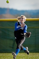 JEROME A. POLLOS/Press..Coeur d'Alene High's Krissy Chissy keeps her eyes on the ball as she races under a Lake City High hit sent to centerfield.