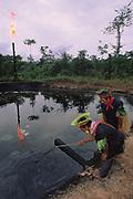 Cofan Indians Inspecting Oil Waste Pit<br />Amazon Rain Forest, Dureno, ECUADOR South America<br />TEXACO WASTE PIT