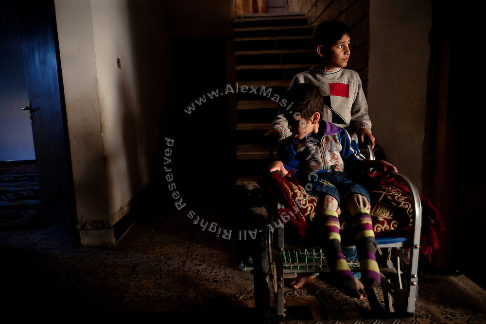 Ali, 10, is assisting one of his two disabled brothers born after the 2004 battles, Ayob, 5, while he is sitting on a wheelchair inside their home in Fallujah, Iraq. The parents and their relatives have no history of birth defects.