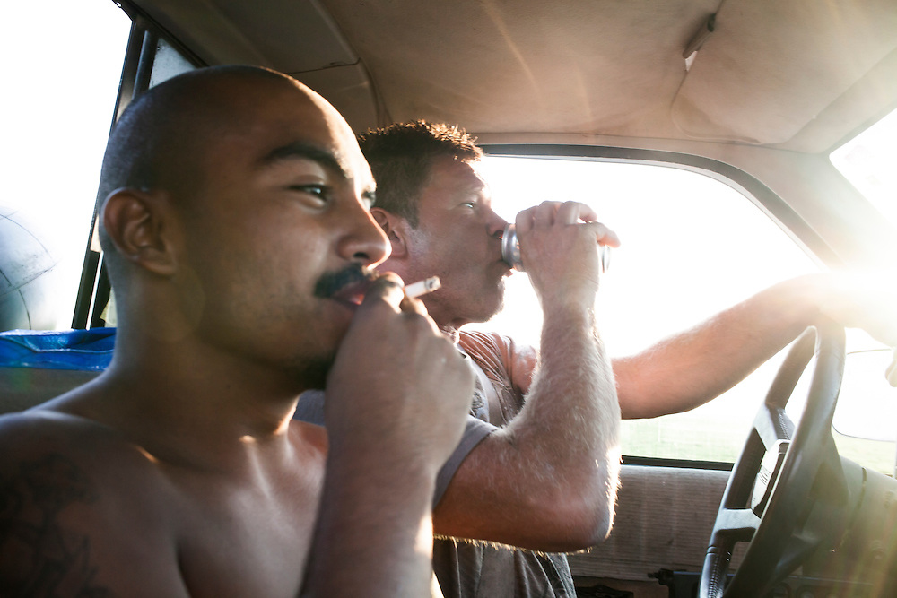 "Alazar ""Junior"" Soto, left, and Steve McFarland smoke and drink in the truck on the way back from tubing on the Des Moines River on Sunday, July 15, 2012 in Webster City, IA."