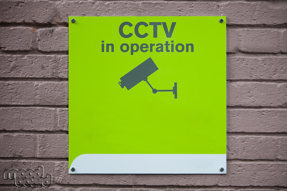 Close-up of 'CCTV in operation' sign on wall