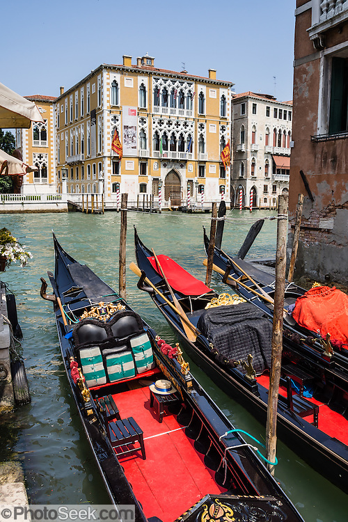 "Gondolas are traditional, flat-bottomed rowing boats which ferry people through Venetian canals. The yellow and white building is Istituto Veneto di Scienze Lettere ed Arti / Palazzo Cavalli Franchetti, which is adjacent to Ponte dell'Accademia bridge on the Grand Canal in Venice. From a peak of 10,000 gondolas 200 years ago, just 500 gondolas now serve Venice. The banana-shaped modern gondola was developed in the 1800s. The left side of a gondola is made longer than the right side to resist leftwards drift at the forward stroke. The gondolier stands on the stern facing the bow and rows just on the right side, with a forward stroke and compensating backward stroke. The oar or rèmo is held in an oar lock, or fórcola, shaped for several rowing positions. The decorative fèrro (meaning iron) ornament on the front can be made of brass, stainless steel, or aluminum, as counterweight for the gondolier standing near the stern. The six horizontal lines and curved top of the ferro represent Venice's six sestieri (districts) and the Doge's cap. Painting gondolas black originated as a sumptuary law eliminating ostentatious competition between nobles. Until the early 1900s, many gondolas had a small cabin (felze) with windows which could be closed with louvered shutters—the original ""venetian blinds."" The romantic ""City of Canals"" stretches across 100+ small islands in the marshy Venetian Lagoon along the Adriatic Sea in northeast Italy, Europe. Venice and the Venetian Lagoons are honored on UNESCO's World Heritage List."