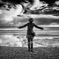 Female youth wearing winter coat and satchel standing alone on beach