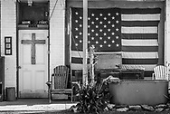 Americana. Photography of American flag and cross on a house in eastern Colorado. USA.